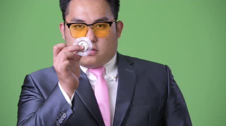fidget spinner : Young handsome overweight Asian businessman against green background
