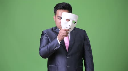 to disguise : Young handsome overweight Asian businessman against green background