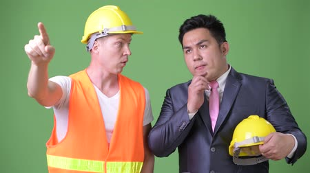 hand on chin : Scandinavian man construction worker and Asian businessman working together