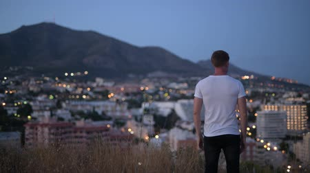 malaga : Rear View Of Young Tourist Man With Arms Raised On Top Of The Hill At Night