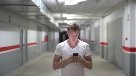 rekesz : Happy Young Man Using Phone Along The Corridor Stock mozgókép