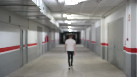 rekesz : Rear View Of Young Man Walking Along The Dark Corridor