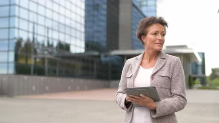 ponderar : Happy Mature Businesswoman Thinking While Using Digital Tablet Outdoors