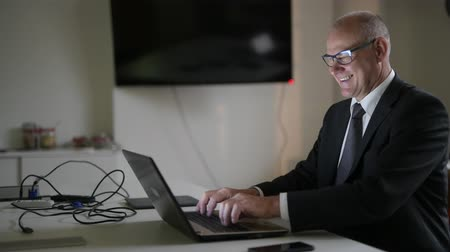 anni sessanta : Happy Senior Businessman Smiling While Using Phone And Laptop At Work