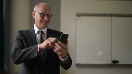 ponderar : Happy Senior Businessman Thinking While Using Phone By The Window At Work Stock Footage