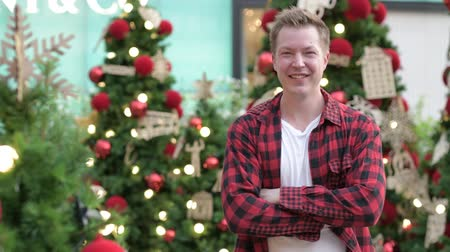 клетчатый : Young Happy Hipster Man Smiling Against Christmas Trees Outdoors