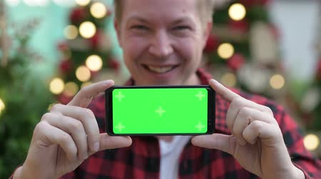 finnish : Young Happy Hipster Man Showing Phone Against Christmas Trees Outdoors