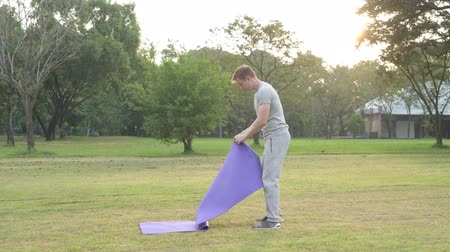 вокруг : Young handsome man setting up yoga mat at the park