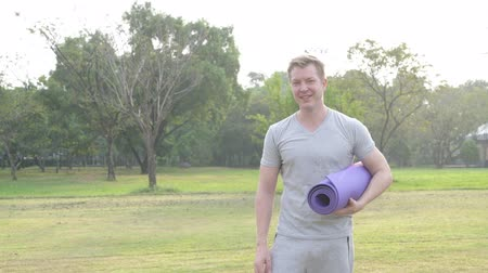 fince : Happy young man thinking while holding yoga mat and giving thumbs up at the park Stok Video