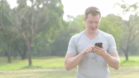 vlogging : Happy young man smiling while using phone at the park Stock Footage