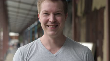 finnish : Face of young happy tourist man smiling at the local pier in Bangkok Stock Footage