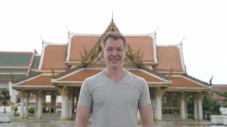 Чеди : Young happy tourist man smiling against view of the Buddhist temple in Bangkok Стоковые видеозаписи