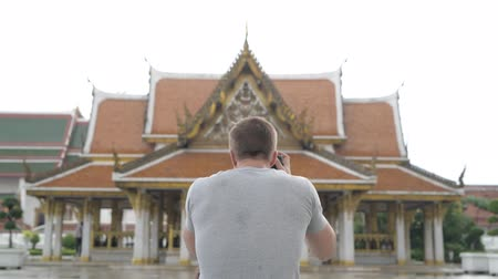 wat : Rear view of young tourist man photographing the view of the Buddhist temple in Bangkok