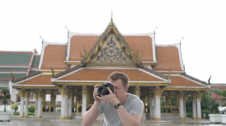 Чеди : Young handsome tourist man taking picture with camera against view of the Buddhist temple in Bangkok