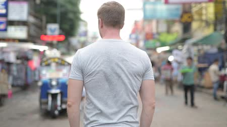fince : Rear view of young tourist man looking around the busy street of Khao San in Bangkok