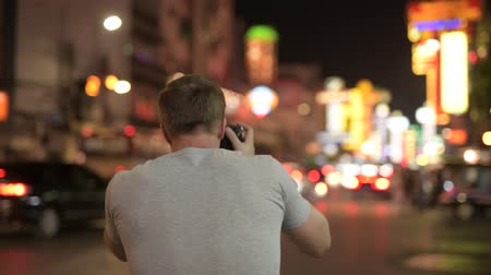 yaowarat road : Rear view of young tourist man photographing the streets of Chinatown at night Stock Footage