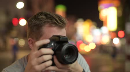 yaowarat road : Face of young tourist man photographing against view of the streets in Chinatown at night