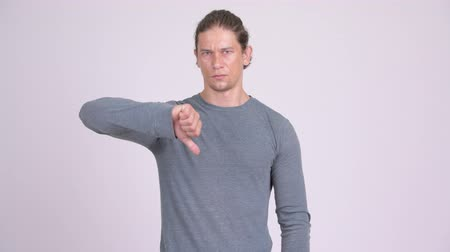 неправильно : Angry man giving thumbs down against white background