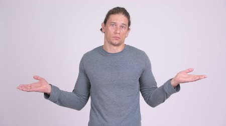 długi : Confused man shrugging shoulders against white background