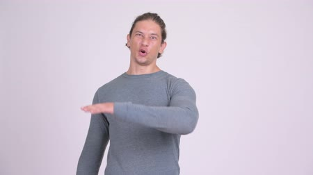 middle : Angry man pointing to camera while talking against white background