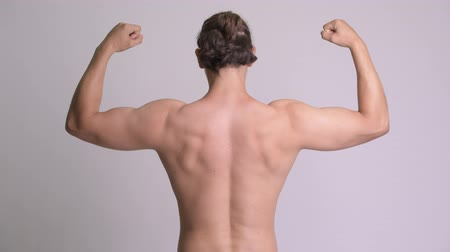 flexão : Rear view of muscular man flexing biceps shirtless against white background