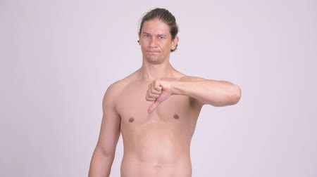 refusing : Angry muscular shirtless man giving thumbs down Stock Footage