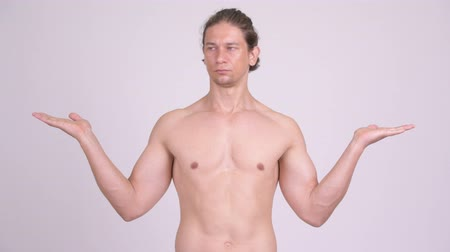 comparar : Handsome muscular shirtless man comparing something