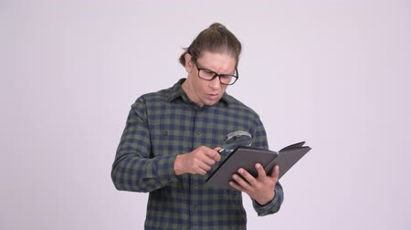 zvědavý : Handsome hipster man reading book with magnifying glass