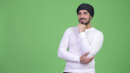 sikhism : Young happy bearded Indian man thinking