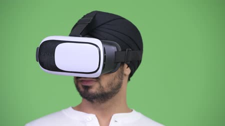 シミュレーション : Young bearded Indian man using virtual reality headset