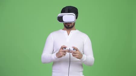 húszas évek : Young bearded Indian man playing games while using virtual reality headset Stock mozgókép