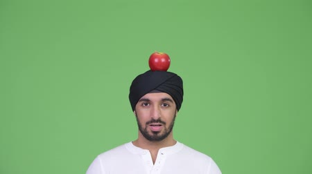 шок : Young surprised bearded Indian man wearing turban with apple on top of head Стоковые видеозаписи