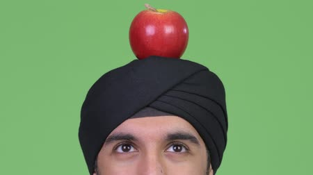 sikhism : Young Indian man wearing turban while thinking with apple on top of head