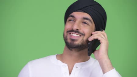 sikhism : Young happy bearded Indian man thinking while talking on the phone