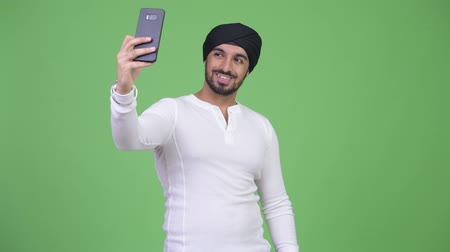 sikhism : Young happy bearded Indian man taking selfie