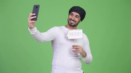 sikhism : Young happy bearded Indian man taking selfie with paper sign