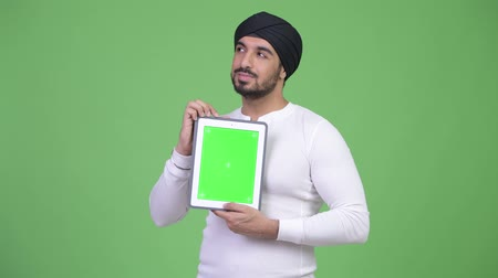 sikhism : Young happy bearded Indian man thinking while showing digital tablet