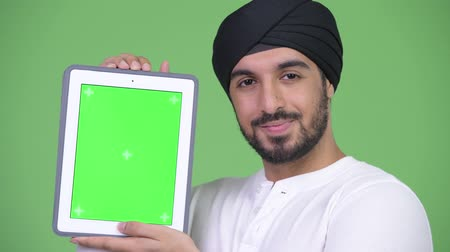 tablet bilgisayar : Young happy bearded Indian man showing and looking at digital tablet Stok Video
