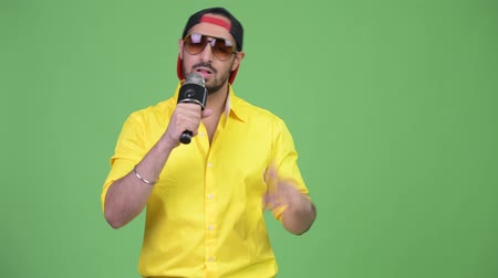 певец : Young bearded Indian businessman rapping with microphone