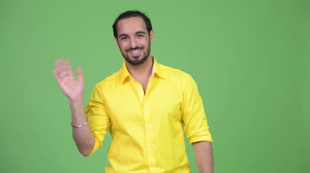do widzenia : Young happy bearded Indian businessman waving hand