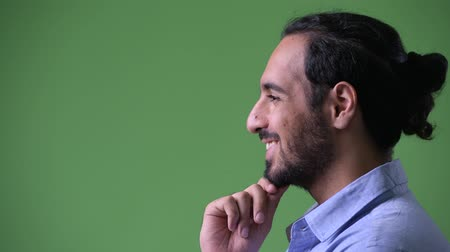ponderando : Profile view of young happy bearded Indian businessman thinking