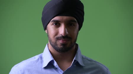 sikhism : Profile view of young handsome bearded Indian businessman wearing turban