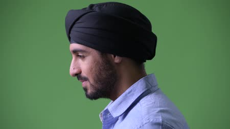 sikhism : Profile view of young handsome bearded Indian businessman wearing turban and looking up Stock Footage