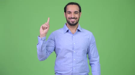 tiro do estúdio : Young happy bearded Indian businessman pointing up Stock Footage