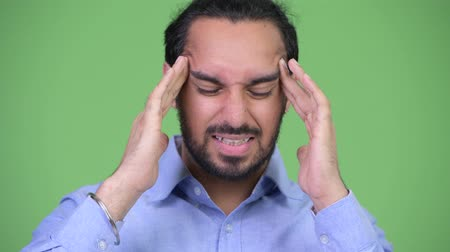 discomfort : Young stressed bearded Indian businessman having headache