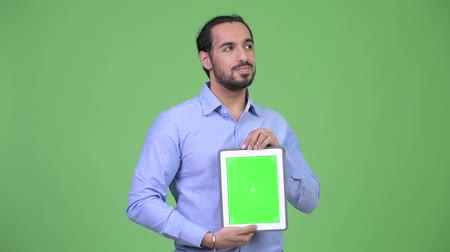 тачпад : Young happy bearded Indian businessman thinking while showing digital tablet