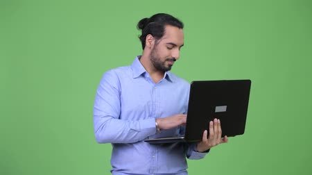 komputer : Young happy bearded Indian businessman using laptop