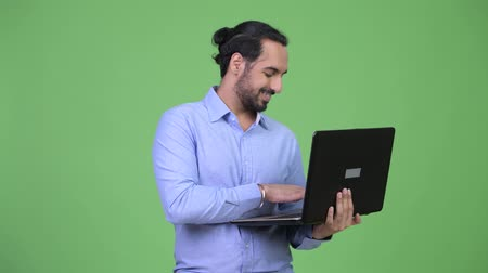 komputer : Profile view of young happy bearded Indian businessman using laptop