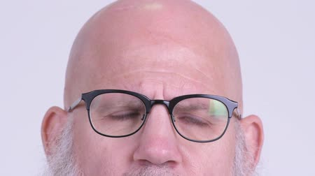 vision care : Eyes of mature bald bearded man with eyeglasses thinking