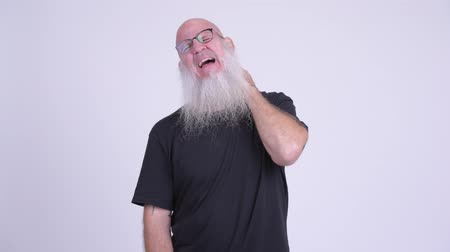discomfort : Stressed mature bald bearded man having neck pain Stock Footage